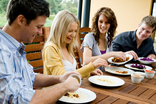 Four young adults having dinner together
